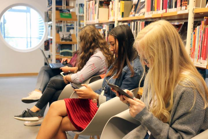 Vier junge Frauen nutzen das Online-Angeboten der Stadtbücherei für Mobilgeräte