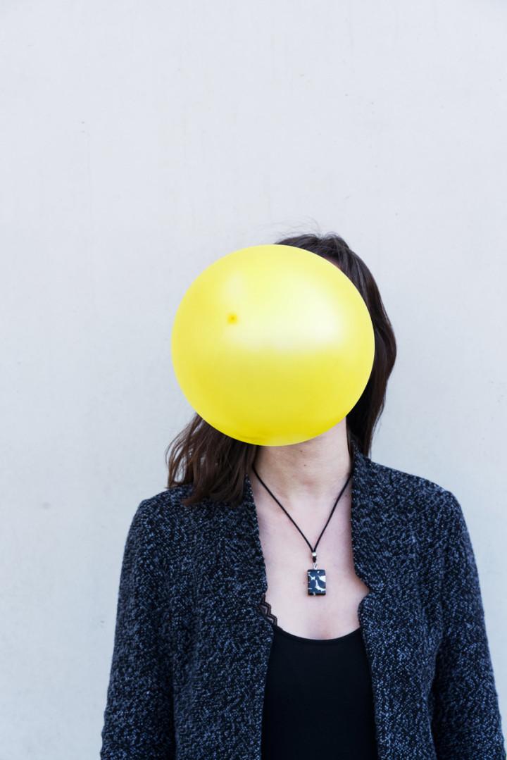 Partrait einer Frau, deren Gesicht von einem gelben Luftballon verdeckt ist.