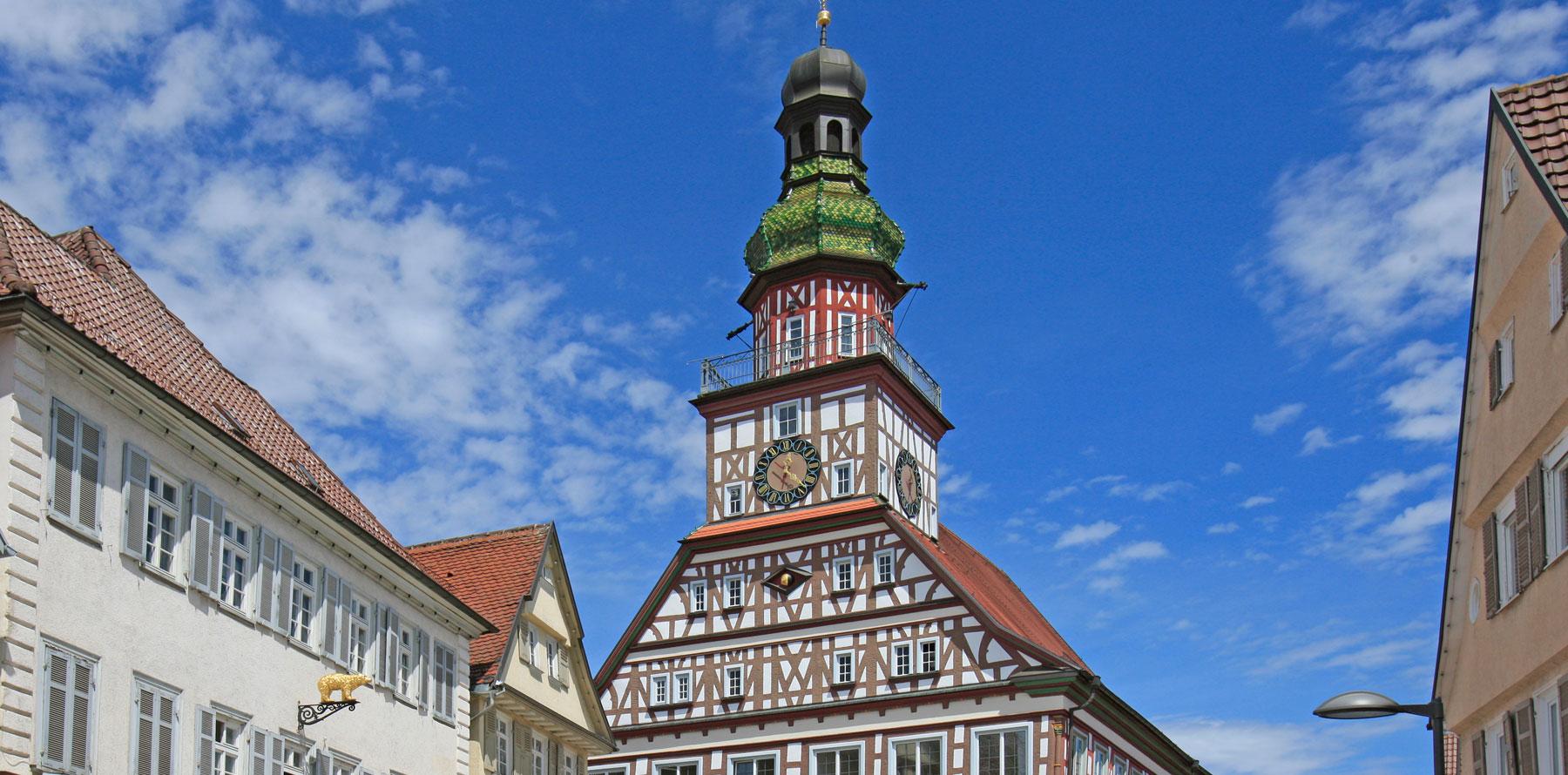 Der obere Teil des historischen Kirchheimer Fachwerk-Rathauses, im Hintergrund blauer Himmel mit wenigen Wolken