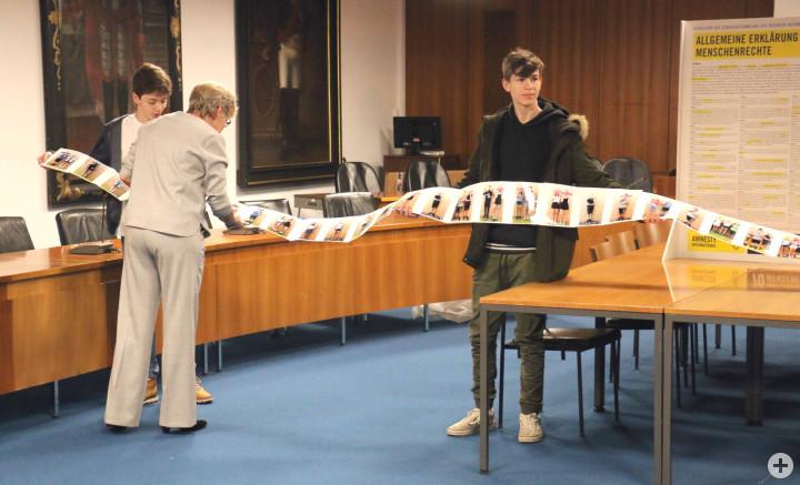 Oberbürgermeisterin Matt-Heidecker betrachtet das ausgeklappte Fotobuch der LUG-Schüler zum Thema Menschenrechte.