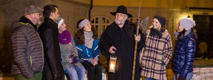 Nachtwächterführung mit einer Gruppe vor dem Kirchheimer Schloss und dem Schlossgraben