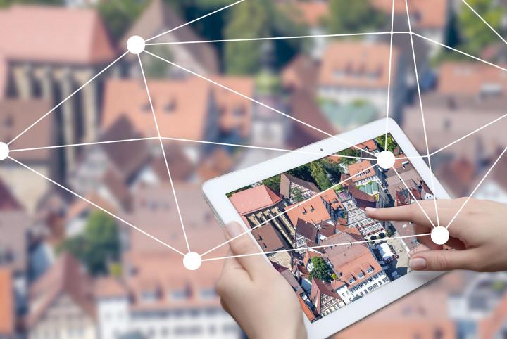 Im Vordergrund ist ein iPad zu sehen. Auf diesem Tablet ist eine Luftaufnahme vom Kirchheimer Rathaus geöffnet. Eine Person hält das Tablet in der Hand. Im Hintergrund ist unscharf eine Stadtaufnahme zu sehen.
