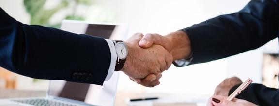 Zwei Personen geben sich gegenseitig die Hand.