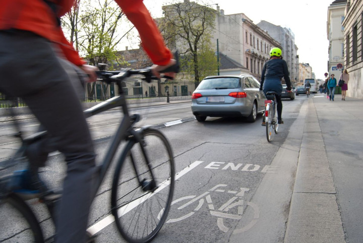 Fahrrad auf einem Fahrradstreifen und vorbeifahrendes Auto