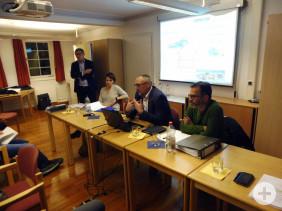 Eberhard Müller von Sachgebiet Grünflächen, Erster Bürgermeister Günter Riemer und zwei Hochwasserschutz-Experten (von rechts) präsentieren auf einer Leinwand Informationen zu Thema Hochwasser.