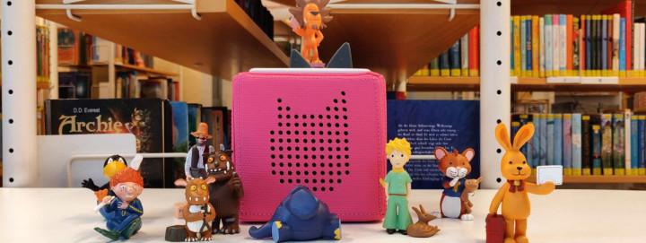 Verschiedene Tonies mit dem Aussehen von Märchen- und Comicfiguren stehen vor, neben und auf einer Toniebox.