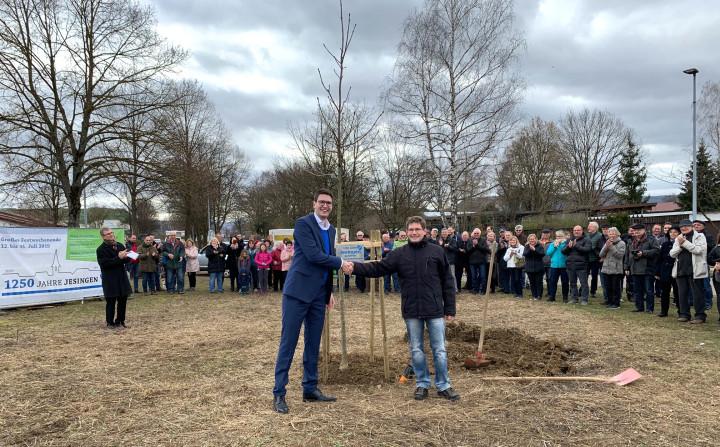 Ortsvorsteher Christopher Flik und Mario Drexler, Vorsitzender Obst- und Gartenbauvereins Jesingen, stehen vor dem frisch gepflanzten Jubiläumsbaum. Im Hintergrund klatschen anwesende Bürger.