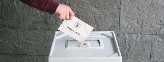 Ein Wahlumschlag wird in eine Wahlurne eingeworfen