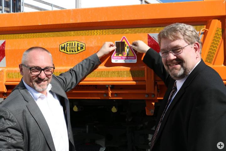 Erster Bürgermeister Günter Riemer befestigt gemeinsam mit Hartfried Wolff, Präsident der Landesverkehrswacht, den ersten Aufkleber an ein städtisches Fahrzeug.
