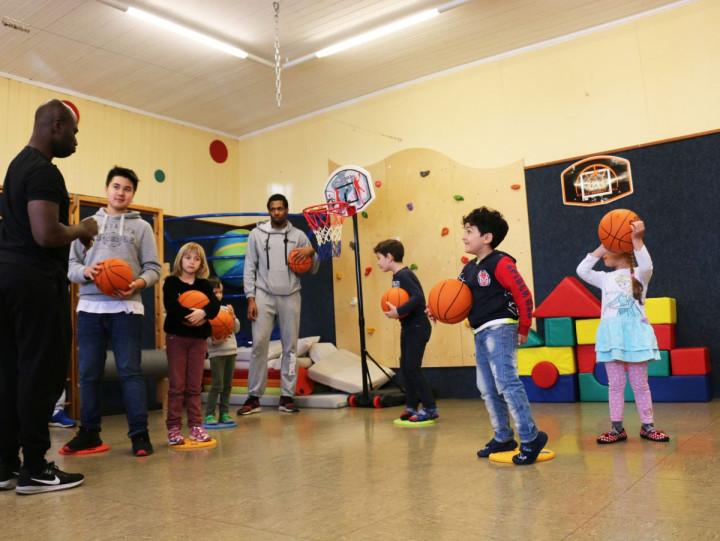 Zwei Spieler der Kirchheim Knights, ein Boys'Day-Teilnehmer und Kinder vom Au-Kindergarten spielen Basketball beim Boys'Day 2019 in der Stadtverwaltung Kirchheim unter Teck