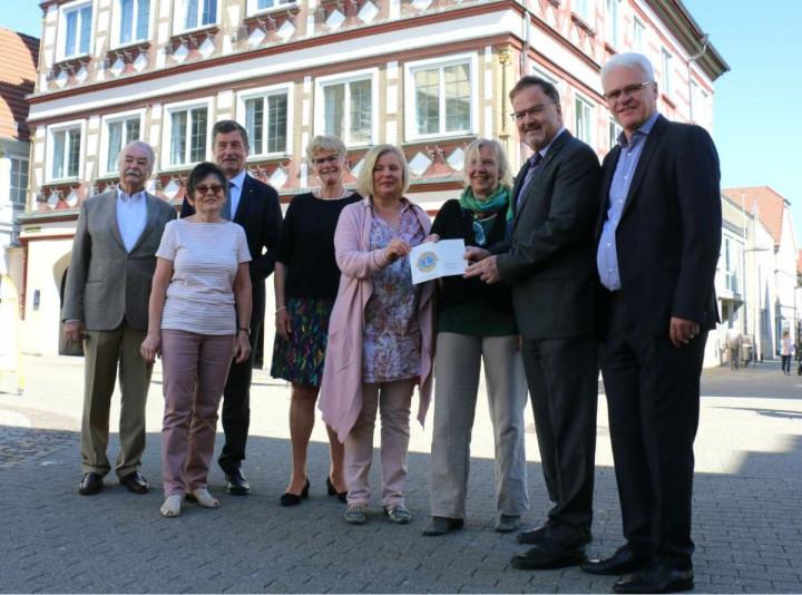 Drei Vorstandsmitglieder des Lions Club Nürtingen-Teck und Oberbürgermeisterin Matt-Heidecker übergeben vor dem Kirchheimer Rathaus den Scheck für das Projekt Wochenendfreizeit für Alleinerziehende mit ihren Kindern an drei der Projektinitiatorinnen.