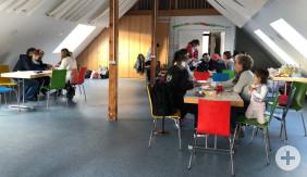 Der Saal im Jesinger Gemeindezentrum. An zwei Tischen sitzen merhere Ehrenamtliche und Geflüchtete.