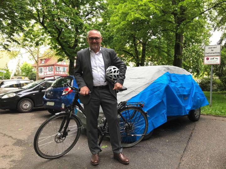 Erster Bürgermeister Günter Riemer steht mit seinem Fahrad vor seinem mit einer blauen Plane bedeckten Dienstwagen.