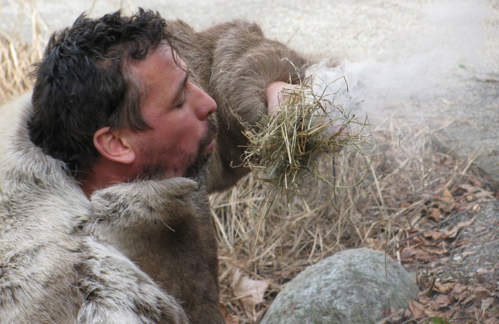 Steinzeitleben: Ein als Steinzeitmensch verkleideter Mann macht Feuer