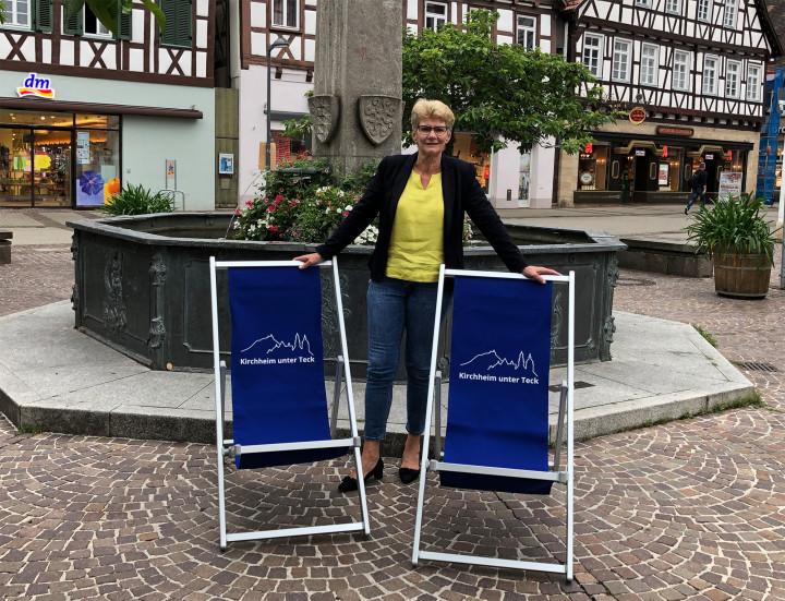 Oberbürgermeisterin Matt-Heidecker steht hinter zwei der neuen Kirchheimer Liegestühle am Marktplatzbrunnen.