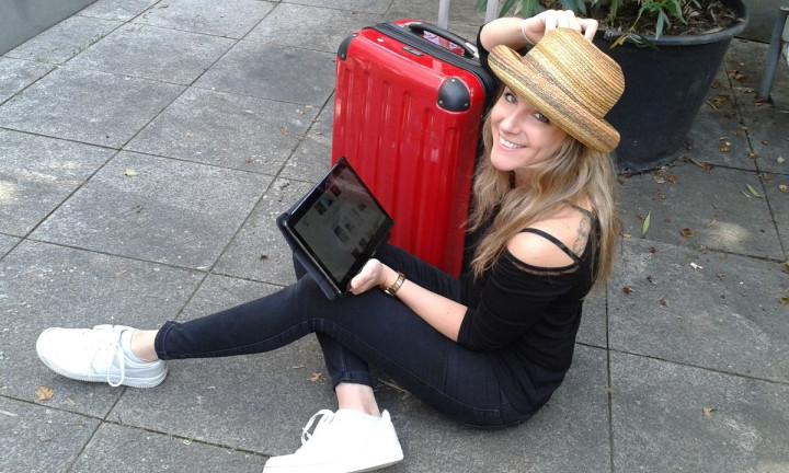 Eine junge Frau sitzt mit ihrem Tablet in der Hand neben einem roten Koffer.