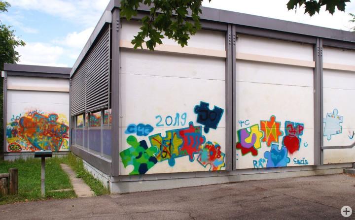 Die weiße Fassade der Haldenschule wurde mit buntem Graffiti in Puzzle-Format besprayt.