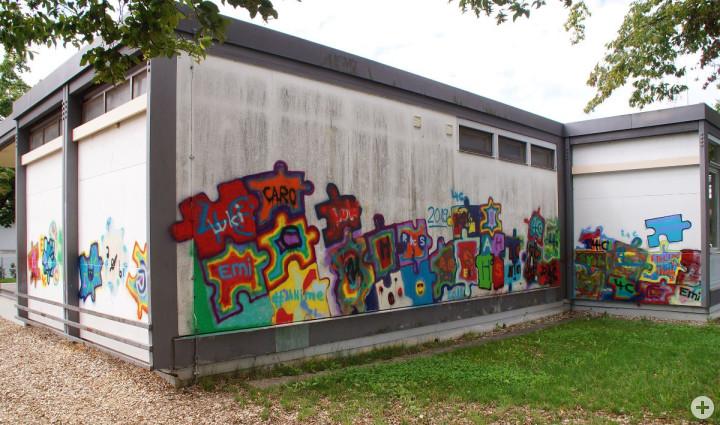 Die Fassade der Haldenschule wurde mit buntem Graffiti in Puzzle-Format besprayt.