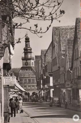 Schwarz-weiß-Bild: Historische Aufnahme aus den 1950er Jahren von der Max-Eyth-Straße mit Menschen und Fahrzeugen. Im Hintergrund ist das Rathaus zu sehen.