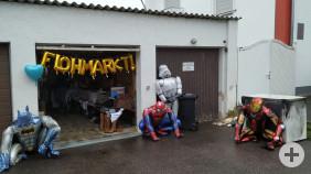 """Eine Garage mit Flohmarktartikeln, unter anderem drei Superhelden-Kostüme, und großem """"Flohmarkt""""-Schriftzug."""