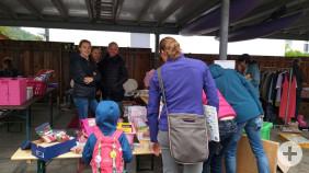 Mehrere Menschen betrachten die Waren eines Standes beim Garagenflohmarkt.