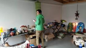 Eine Frau durchstöbert das Angebot an einem Stände bei Garagen-Flohmarkt.