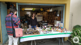 Eine Frau betrachtet die Waren an einem Stand des Garagenflohmarktes.