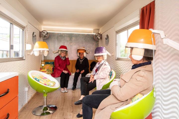 Geschichten unter der Haube: Vier Frauen lauschen den Geschichten des Pop-Up-Salons unter den Friseur-Hauben.