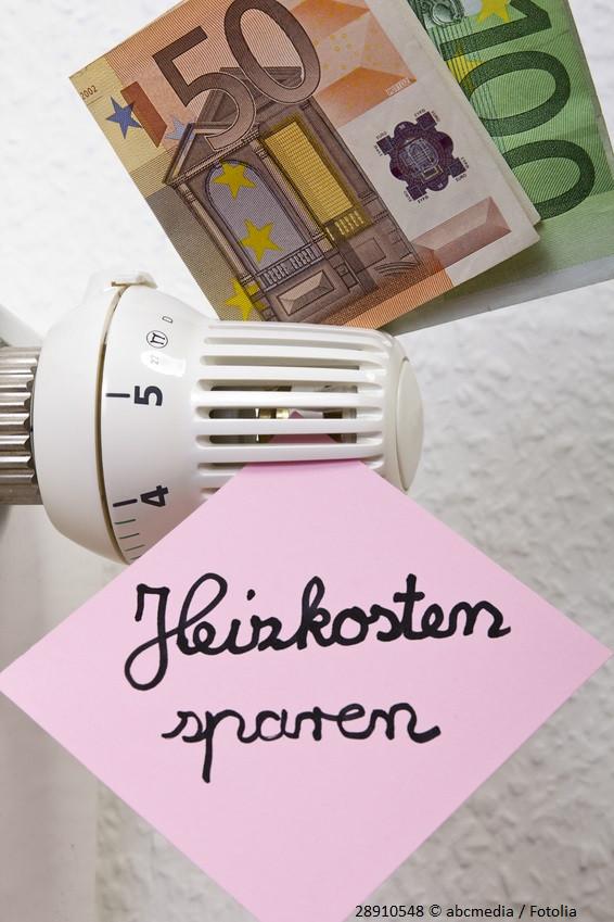 """Ein Heizkörper, an dem ein Zettel mit der Aufschrift """"Heizkosten sparen"""" sowie ein 50- und ein 100-Euro-Schein geklemmt sind."""