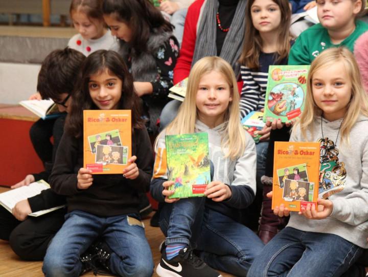 Schüler der Alleenschule zeigen gespendete Bücher der Bildungsstiftung der Kreissparkasse für den Landkreis Esslingen