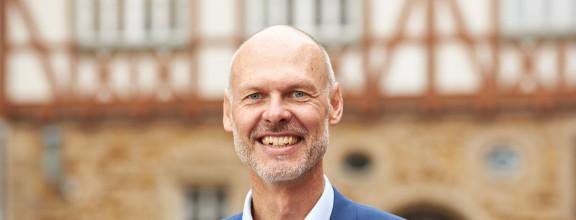 Portrait von Oberbürgermeister Dr. Pascal Bader vor einem Fachwerkgebäude in der Kirchheimer Innenstadt