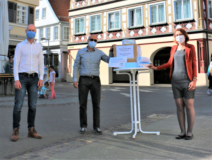 """Oberbürgermeister Pascal Bader und Monika Schober vom Verein """"Gemeinsam statt Einsam e.V."""" nehmen eine Maskenspende von Rolf Hirsch, Geschäftsführer von Hiro Innovation+Projekt Design aus Dettingen auf dem Platz vor dem Rathaus entgegen."""