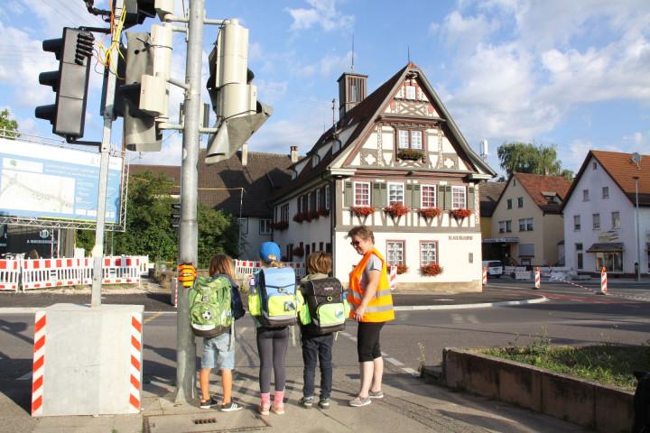 Bild einer Schülerlotsin mit drei Kindern an einer Ampel