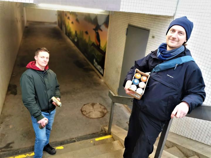 Die Graffiti-Künstler Stefan Fischer und Christian Pomplun auf der Treppe der Unterführung vor ihrem Kunstwerk.