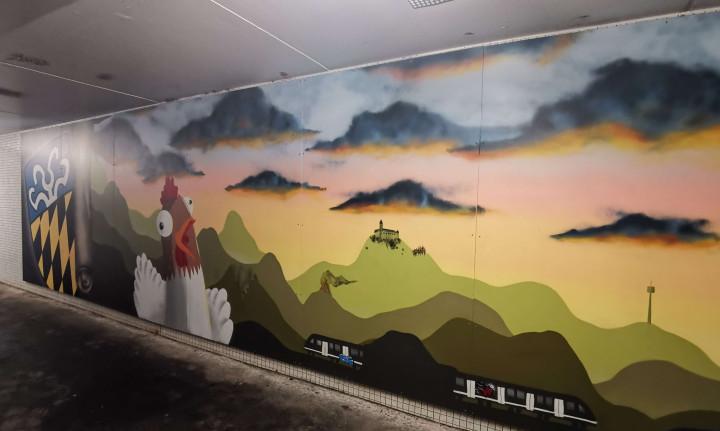 Graffiti-Kunst am Bahnhof Ötlingen: Links das Wappen des Ortsteils Ötlingen, gefolgt von einem Rotgockel und einer Hügellandschaft mit verschiedenen Details wie der Burg Teck, dem Fernsehturm und einer angedeuteten S-Bahn.