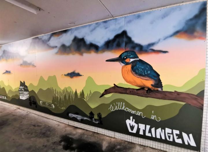 """Graffiti-Kunst am Bahnhof Ötlingen: Zu erkennen ist das Rathaus von Ötlingen, die angedeuteten Bürgerseen, sowie ein bunter Vogel auf einem Ast vor einer Hügellandschaft, gemeinsam mit dem Schriftzug """"Willkommen in Ötlingen""""."""