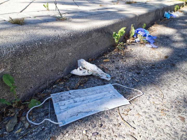 Eine weggeworfene medizinische Maske liegt auf der Straße