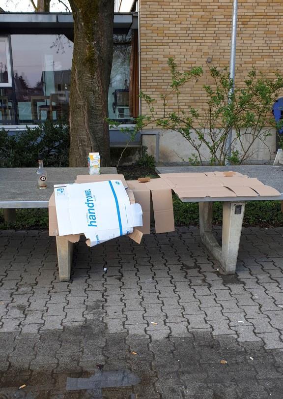 Auf einer Tischtennisplatte auf dem Gelände der Kirchheimer Eduard-Mörike-Schule liegen Kartons und leere Flaschen.