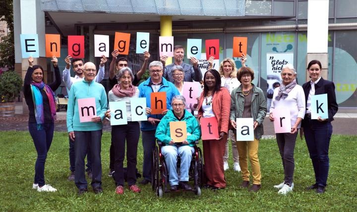 """Ehrenamtlich Engagierte halten Buchstaben in die Luft, die den Schriftzug """"Engagement macht stark!"""" bilden."""