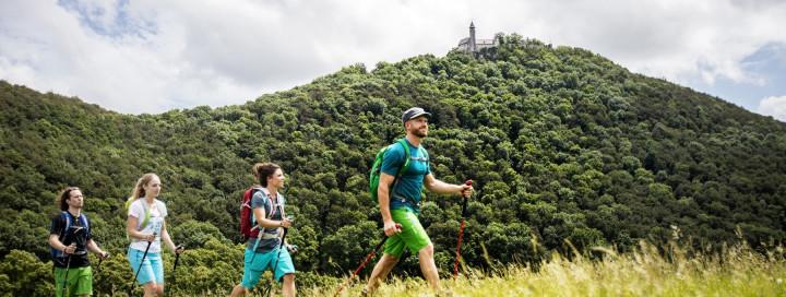 Blick auf vier hintereinanderlaufende Wanderer vor der Burg Teck