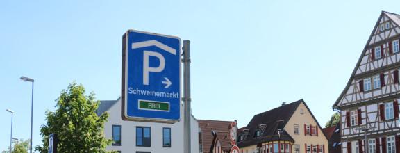 """Schild mit der Aufschrift """"Parkhaus Schweinemarkt"""" vor blauem Himmel"""